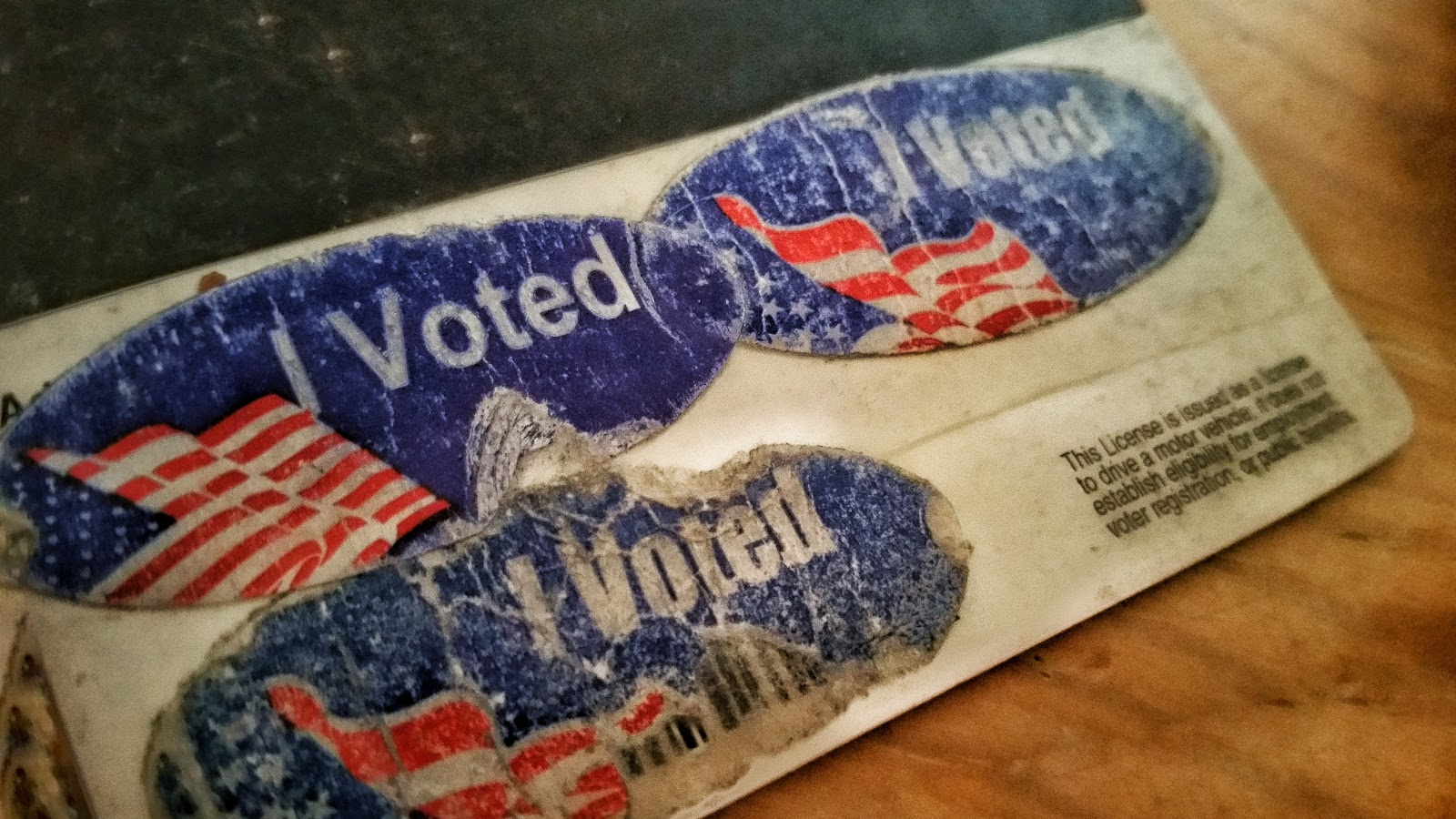 "Crusty and gnarled ""I voted"" stickers on the back of a license."