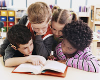 four children huddled around a book reading