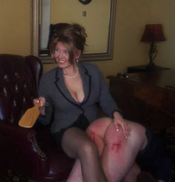 smiling woman in business suit spanking man with a paddle