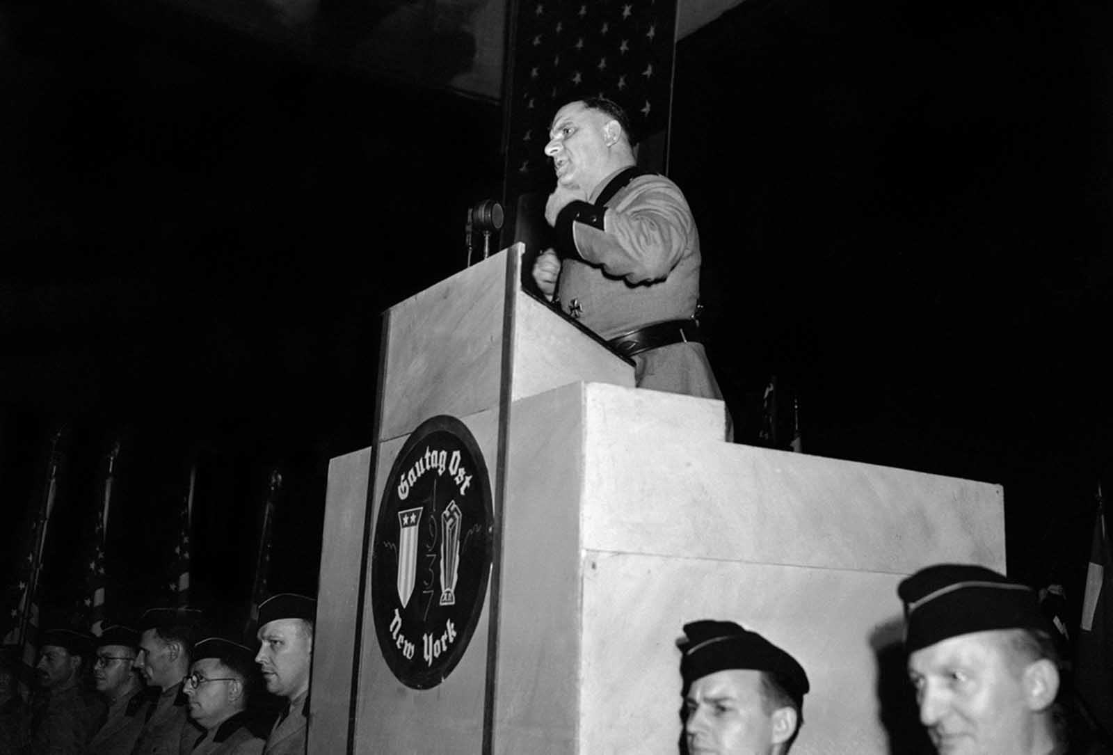 Original Caption: Fritz Kuhn, in the full uniform of a Storm Trooper, national leader of the Bund gestures from the rostrum at Madison Square Garden in New York, on February 20, 1939 while he uttered imprecations against Jews over and over.