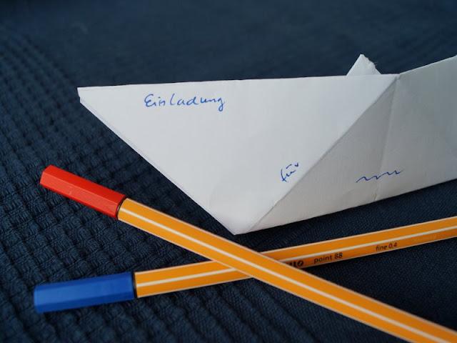 DIY: Papierschiff-Einladungen für den Kindergeburtstag basteln. Ihr beschriftet und verziert die Schiffe aus Papier und stattet sie mit Mast und Segel aus, dann können die Einladungen den Anker lichten.