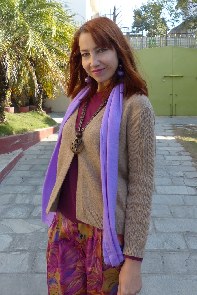 Brownish cardigan over magenta top with lilac scarf and earrings