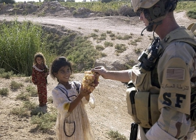A USA soldier giving grapes to Iraq children.