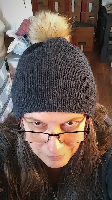 Hand knit charcoal gray hat with faux fur pompom