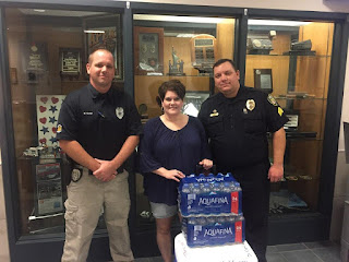 Cindy poses with 2 police officers with water