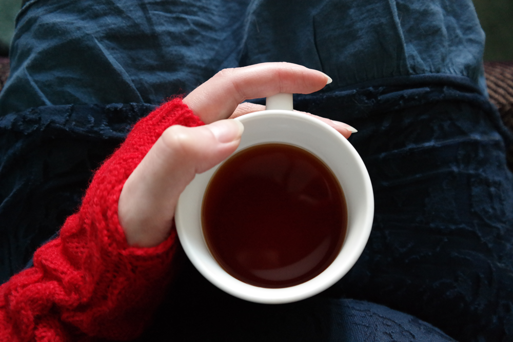 Hand in wrist warmers holding cup of tea