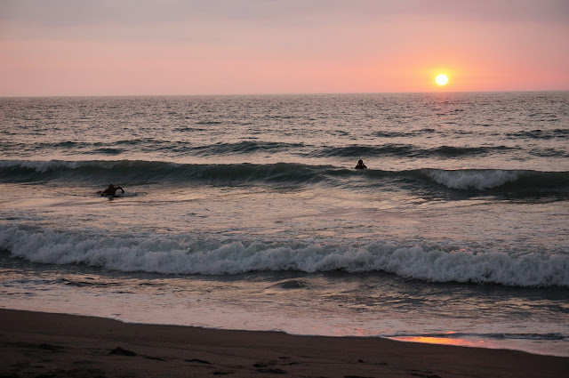 Sunset from the beach at Liwliwa, Zambales with a couple of surfers trying to get a wave