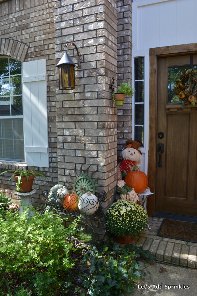 .Planter filled with pumpkins, bench, scarecrow, Mums, Lanterns on Porch