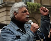 British-Pakistani Journalist Tariq Ali with raised fist and a microphone