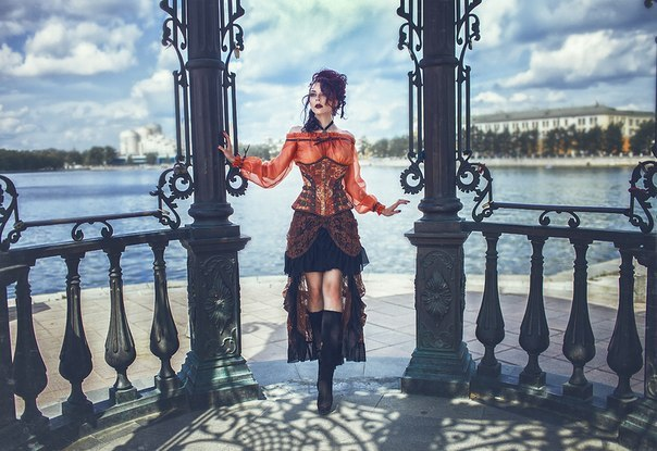 Steampunk fall fashion in shades of autumn: orange, brown and black with red hair. Skirt, corset, peasant blouse, jeweled hairpiece.
