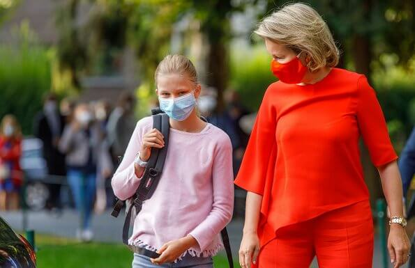 Queen Mathilde wore an Adria asymmetric jumper and Milan trousers, both by Natan, which she had worn before. Princess Eleonore