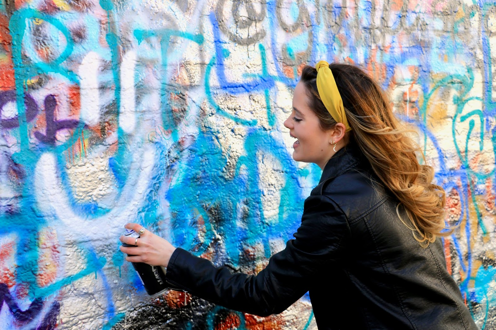 Kathleen Harper spray painting a wall on Graffiti Street in Gent, Belgium