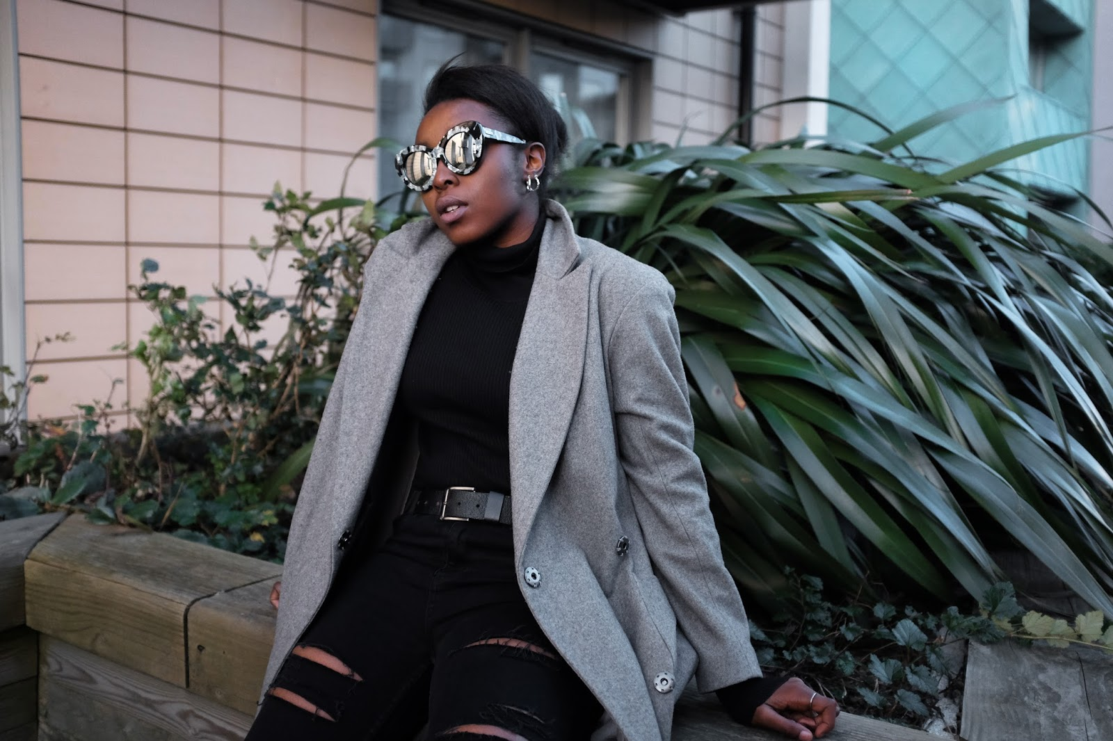 Fashion blogger wearing Go Go Go LeSpecs sunglasses long grey asos coat ripped black jeans