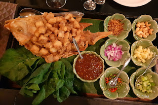 Tipico antipasto thailandese: pesce fritto con diversi condimenti da mangiare in un cono di foglia