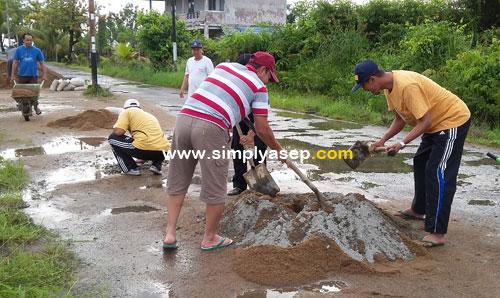 ADUK SEMEN :  Warga mengaduk adonan semen untuk mengecor jalan jalan yang berlubang. Foto Asep Haryono