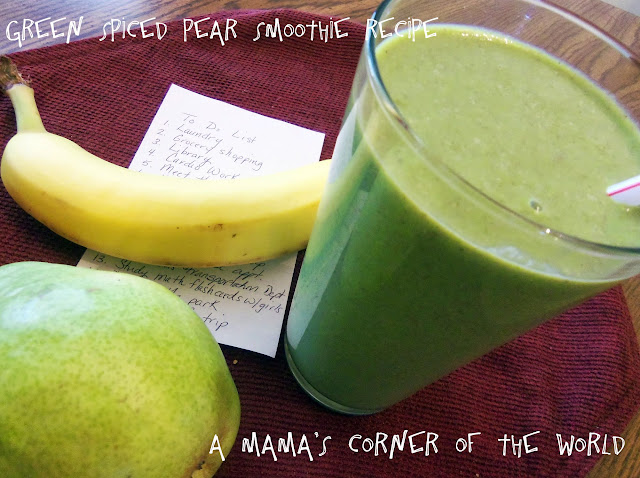 Green spiced pear smoothie in a glass with a fresh pear and a banana