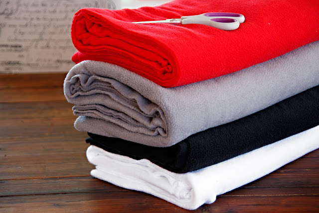 Stack of polar fleece fabric for tug toy making (white, black, grey and red fleece)
