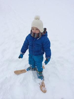 Niño abrigado en la nieve con esquís