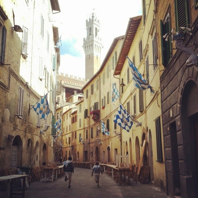 A medieval road in adorned with blue and white flags for the Palio di Siena