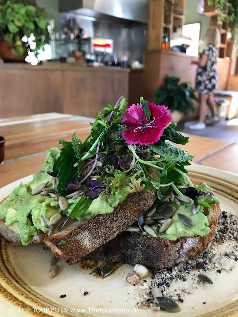 Avocado on sourdough decorated with edible flowers served on a light green plate. A woman in a summer dress orders food at a coffee counter in the background.
