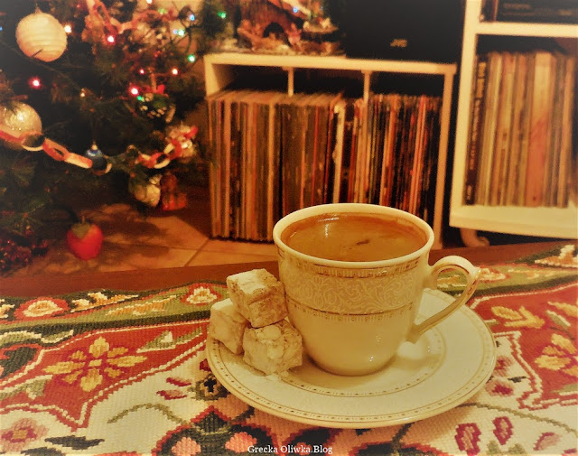 na stole w białej porcelanowej filiżance kawa z pianką po grecku z tureckimi delicjami w tle świąteczna choinka oraz gramofonowe płyty
