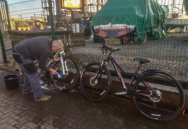 Photo of Phil scrubbing our bikes before I hosed them off