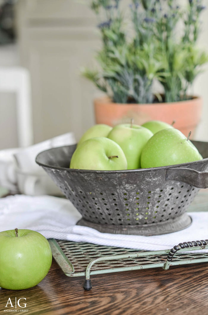 Create a simple farmhouse centerpiece by displaying apples in a vintage colander.  |  www.andersonandgrant.com