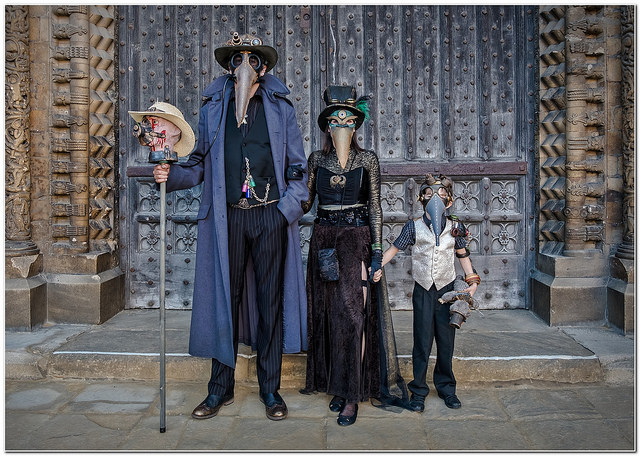 Family of cosplayers dressed as steampunk plague doctors with leather bird masks (mom, dad, kid)