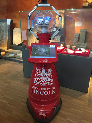 Red anthropomorphic robot with University of Lincoln logo on body