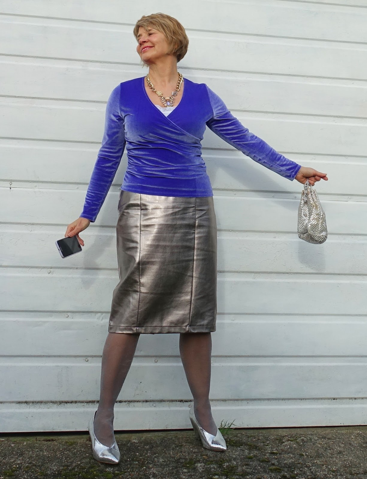 Image showing a middle aged woman posing against a white garage door wearing silver skirt and shoes and an iris blue velvet top