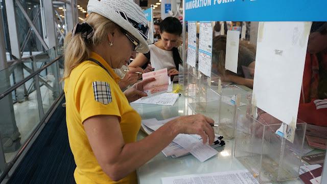 На фото - Туристка у регистрационной стойки в аэропорту