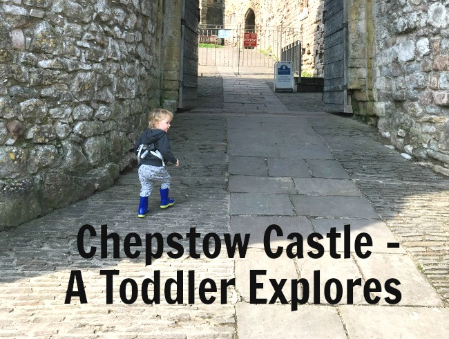 Chepstow Castle - A Toddler Explores written across picture of toddler at castle entrance