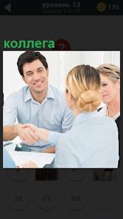За столом коллеги после сделки пожимают руки друг другу