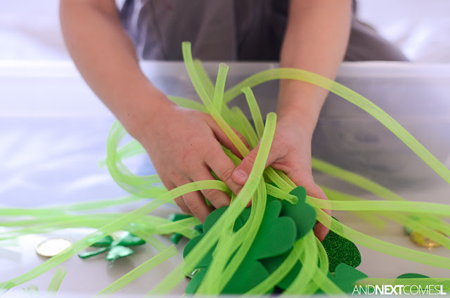 Playing with a St. Patrick's Day sensory bin from And Next Comes L