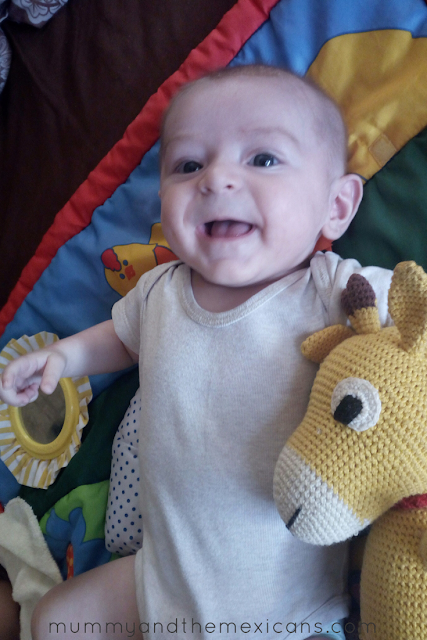 Life With Baby At 4 Months Old - Image Shows Baby Smiling And Clutching Stuffed Toy