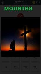 В сумерках еле заметный силуэт человека на коленях осуществляющий молитву перед стоящим крестом