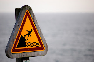 warning sign with human figure falling off a cliff