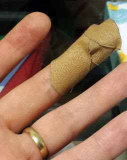 A close up image of a woman's left hand with a gold wedding band on the ring finger and a bandage on the middle finger.