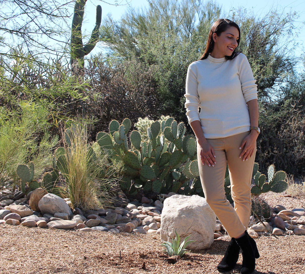 This is a photo of me with my head turned to the left, rocking my J. McLaughling outfit with a white sweater, caramel jeans and black velvet ankle boots in the desert.