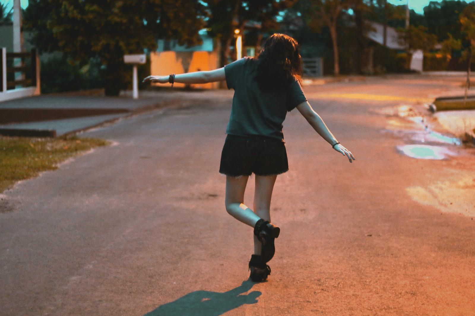garota andando na linha da rua