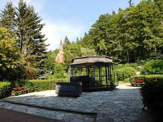 """Źródło """"Pieniawa Chopina"""", a za nim kościół zdrojowy Najświętszego Serca Pana Jezusa z 1904 roku."""