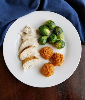 looking down on round dinner plate with duchess sweet potatoes, turkey and roasted brussels sprouts