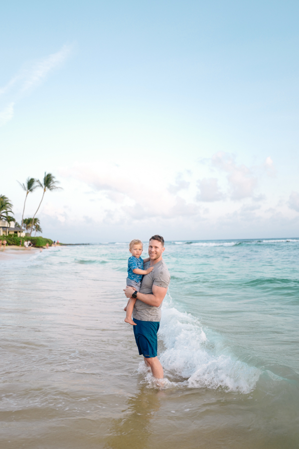 father-son moment and beautiful blue-green waters at Poipu Beach, Kauai