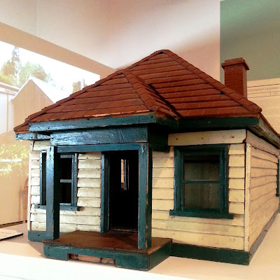 1930s vintage dolls' house bungalow on display in a museum gallery, showing the front and side.