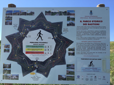 Palmanova sign explaining walking and biking routes and distances.