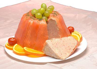 Mousse de salmón ahumado en un plato. Mousse entero con un trozo cortado. Contiene uvas, rodajas de naranja y tomates cherry decorando.
