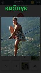 Девушка на каблуках пытается встать на канате на большой высоте