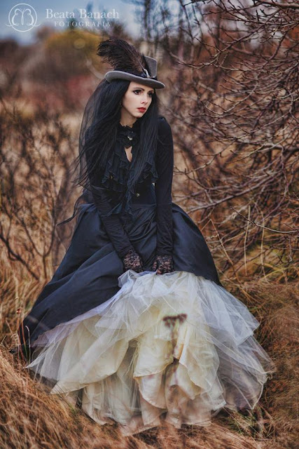 Gothic Victorian woman in black skirt, corset, and ruffle blouse. She wears a gray hat with a large feather