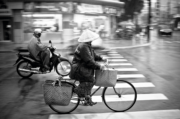 These two photographs share the same action they are both images of people riding bikes the first photograph is panning when everything is in motion