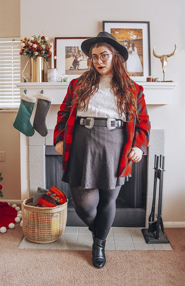 A woman with brown wavy hair wearing a black wide brim fedora, white pleated Victorian inspired blouse, a red and black buffalo plaid coat, a black short skater skirt, a black and silver western belt, black tights and black heeled ankle Chelsea boots